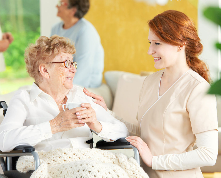 senior woman holding a cup of tea talking to her caregiver