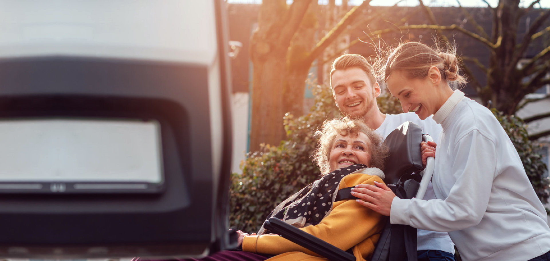 young couple helping senior woman get into the van