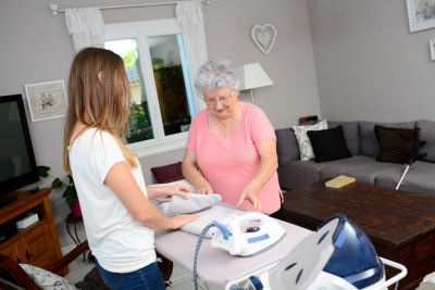 Young woman ironing and helping with household chores an senior